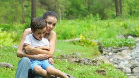 Mother hugs her son near a stream stock footage