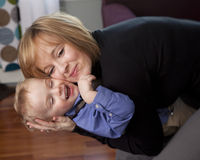 Mother hugs son. Beautiful young mother holds her young son close in a hug stock photography