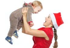 Mother i Santas som hatten som leker med, behandla som ett barn Royaltyfria Foton