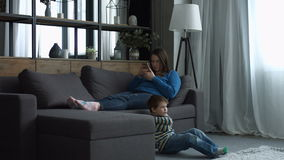 Mother ignoring her little boy in the bedroom. Busy mother surfing the net on smartphone and ignoring her little boy at home. Sad preschool kid sitting on floor stock video