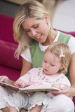 Mother In Living Room Reading Book With Baby Stock Photos