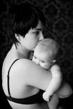 Mother and infant calm and gentle embrace. Mother and infant calm and gentle hug, infant buried his mother in the shoulder and quietly looking at the light, the Stock Photo