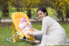 Mother with infant in chair Stock Photography
