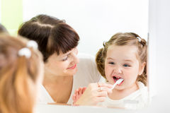 Mother instructing kid teeth brushing Stock Images