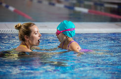 Mother or instructor teaching little girl to hold breath before. Diving in pool Royalty Free Stock Images
