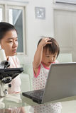 Mother introduce technology to her daughter. With laptop and microscope Royalty Free Stock Image