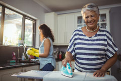 Mother ironing clothes while daughter washing utensil Stock Image