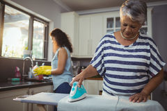 Mother ironing clothes while daughter washing utensil Royalty Free Stock Photography