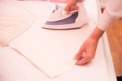 Mother ironing little dress. Mother hands ironing dress for little girl Royalty Free Stock Photos