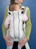 Mother keeps the child in a baby sling Royalty Free Stock Images