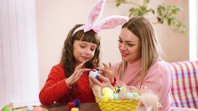 The mother keeps the egg, and paints his daughter and throws his hands wondering. The mother keeps the egg, and paints his daughter and throws his hands stock video footage