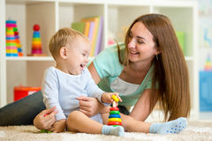 Mother and kid boy play together indoor at home Royalty Free Stock Photos