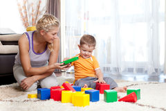 Mother and kid boy playing together indoor. Cute mother and kid boy playing together indoor Stock Photos