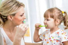 Mother and kid brushing teeth Stock Image
