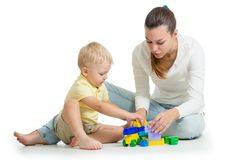 Mother and kid build out of colorful plastic blocks. Family and childhood concept. Isolated on white background royalty free stock image