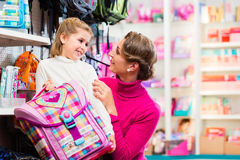 Mother and kid buying school satchel or bag in store. Mother and kid becoming a student buying school satchel or bag in store Royalty Free Stock Photos