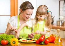 Mother and kid cook in the kitchen Stock Images