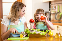 Mother and kid cooking and having fun in kitchen Stock Photos