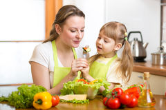 Mother with kid cooking and tasting of food Royalty Free Stock Photos