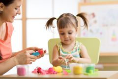 Mother and kid daughter at home molded from clay and play together. Concept of preschool or home education. Stock Images