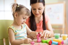 Mother and kid daughter at home molded from clay and play together. Concept of preschool or home education. stock photography