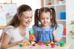Mother and kid daughter at home molded from clay and play together. Concept of preschool or home education. Royalty Free Stock Image