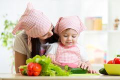 Mother and kid daughter knife cut cucumber Royalty Free Stock Image