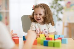 Mother and kid daughter playing colorful block toys at home Royalty Free Stock Photo