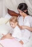 Mother and kid daughter read a book together in bed. Happy mother and kid daughter read a book together in bed Stock Photos