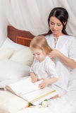 Mother and kid daughter read a book together in bed. Happy mother and kid daughter read a book together in bed Stock Photo