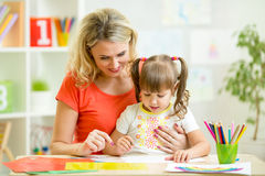Mother and kid drawing with pencils together Royalty Free Stock Photography