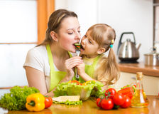 Mother and kid eat vegetables in kitchen Stock Images