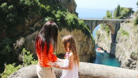 Famous fiordo di furore beach seen from bridge. Mother and kid enjoy the amazing view of Fiordo di Furore. Cala di Furore beach, bridge over the gorge Fiordo di stock footage