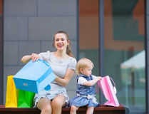 Mother and kid examines purchases after shopping Stock Images