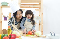 Mother and kid girl cooking and cutting vegetables Stock Photos