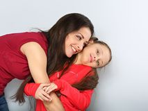 Mother and kid girl hugging with happy emotional faces on blue background stock image