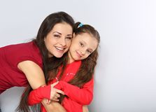 Mother and kid girl hugging with happy emotional faces on blue background with empty copy space stock photo