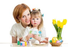 Mother and kid girl paint Easter eggs. On white royalty free stock image