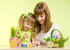 Mother and kid girl paint easter eggs. Mother and kid girl painting easter eggs together Stock Photo