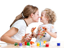 Mother and kid girl painting and having fun. Happy mother and kid girl painting and having fun stock photography