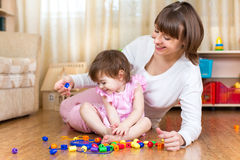 Mother and kid girl play toys at home Stock Photo