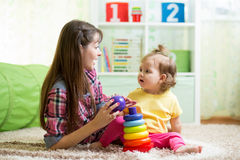 Mother and kid girl playing together indoor at home. Cute mother and kid girl playing together indoor at home Stock Images