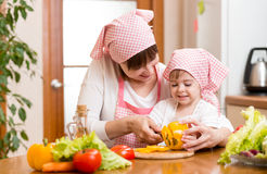 Mother and kid girl preparing food to lunch Royalty Free Stock Image