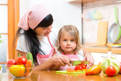 Mother and kid girl preparing healthy food. Mom and kid girl preparing healthy food royalty free stock image