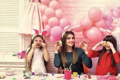 Mother and kid girls paint easter eggs. At pink balloons stock image