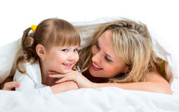 Mother and kid lying under the blanket in bed Royalty Free Stock Photo