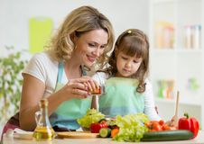 Mother with kid make salad Stock Images