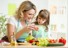 Mother with kid make salad stock photography