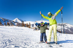 Mother and kid in masks standing with arms up. Mother and kid in masks standing on the snow hill with ski polls and  with arms up Royalty Free Stock Photo