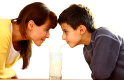 Mother and kid with milk. A mother and her child drinking milk looking each-other from a glass with straws isolated on a white background Stock Photo